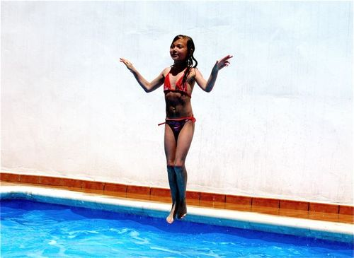 Girl jumping in pool like angel, Spain