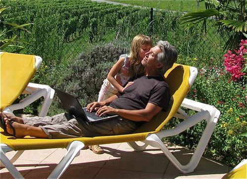 Bordeaux vineyards kiss digital nomad family dad & daughter & laptop pool side