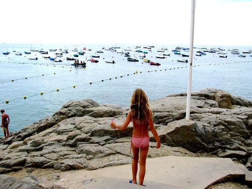 Costa Brava, Spain, girl on cliff, beach and boats