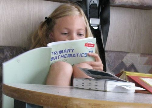 girl doing homeschool roadschool world school in RV motorhome Europe family travel