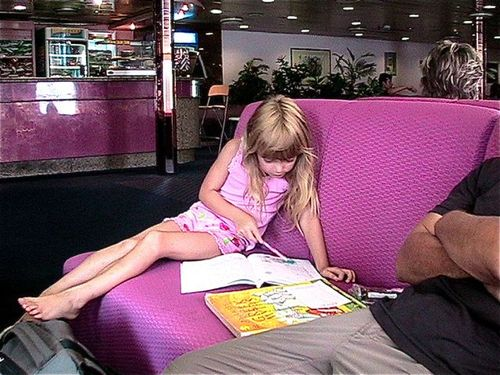 young girl doing homeschool on ferry between Greece and Turkey backpacker RTW Family travel