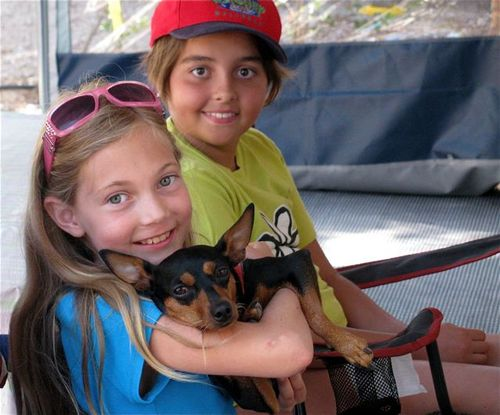 two tween travelers with a dog in campground in Barcelona making friends in Europe