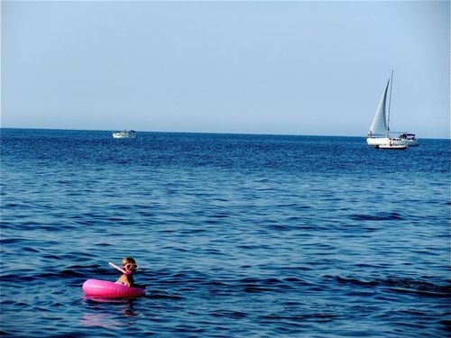 French riviera family travel blue sea, pink tube, boats