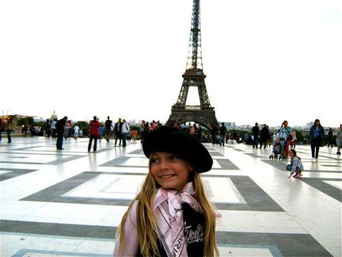 Tween at Eiffel Tower, family travel Paris, beret & scarf souvenirs