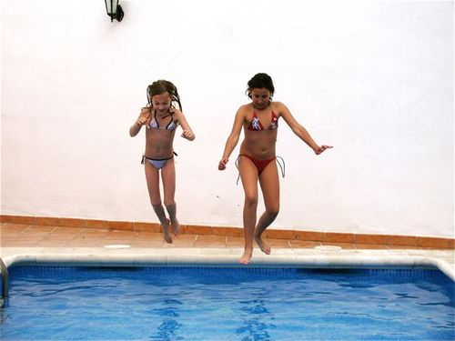 2 girl jumping in pool in spain, andalusia, costa del sol