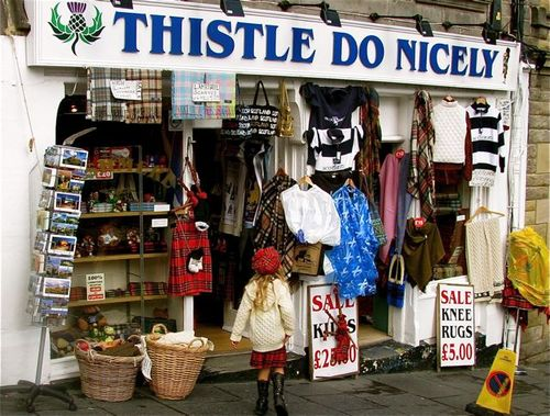 Family travel in Edinburgh, Scotland, funny signs, Edinburgh festival in kilt and tam at souvenir shop