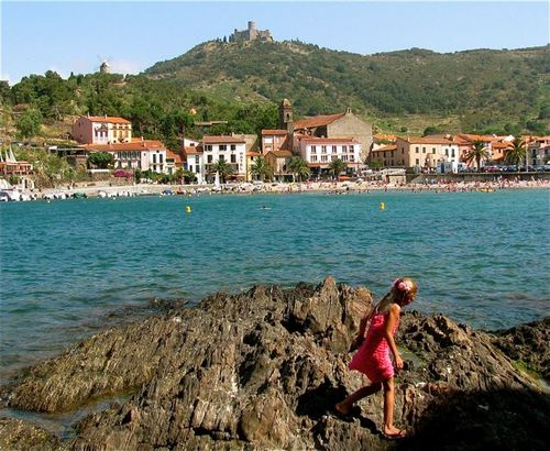Family travel in France girl on rocks on Vermeille Coast in Collioure