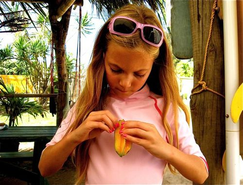 kidlet eating first star fruit in Hawaii