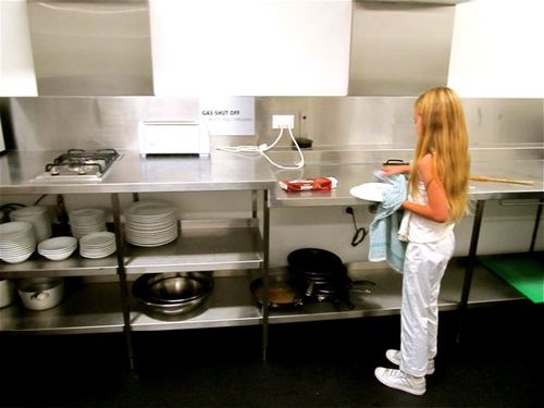 kiddo drying dishes at hostel in sydney