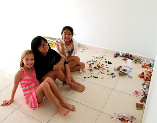 trilingual trio of tweens in Asia playing with tiny toys