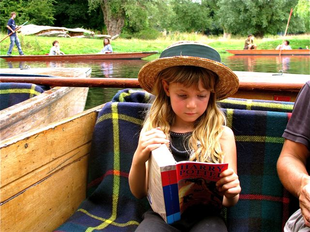 Our 7 year old reading Harry Potter on a punt in Cambridge, UK