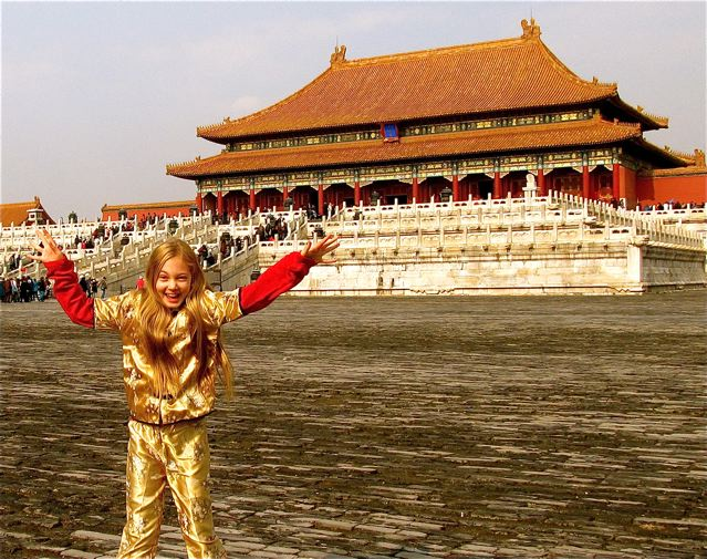 Jumping for joy in Beijing in traditional Chinese clothes at Forbidden City