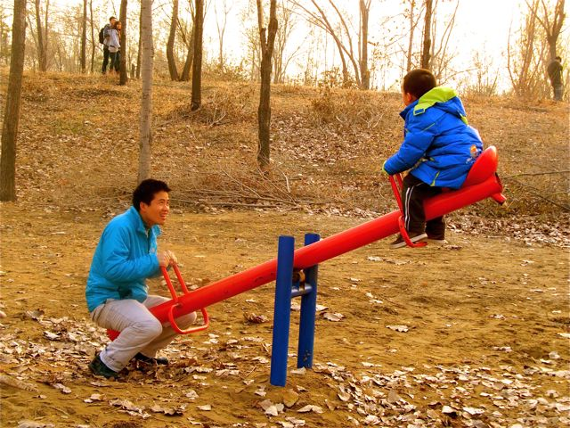 Playing in a Beijing park, Andrew and his dad on seesaw