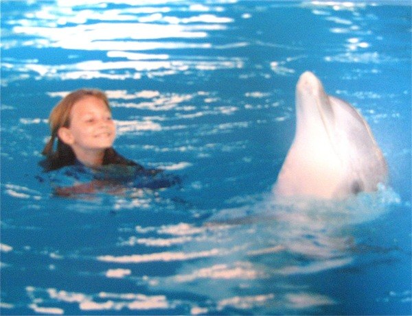 cute little girl swimming with dolphin