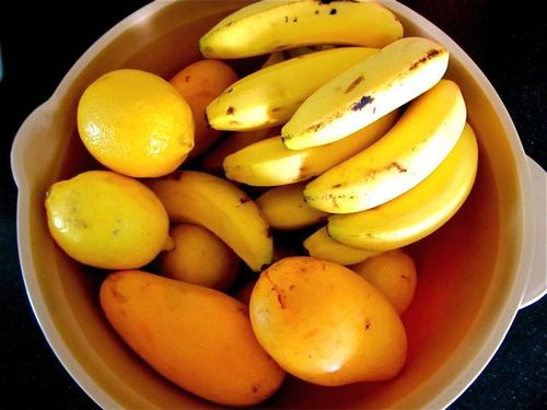 mangos, bananas and lemons in a bowl