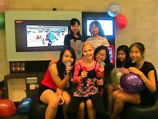 American girl with her Mandarin speaking friends at Karaoke party in Asia