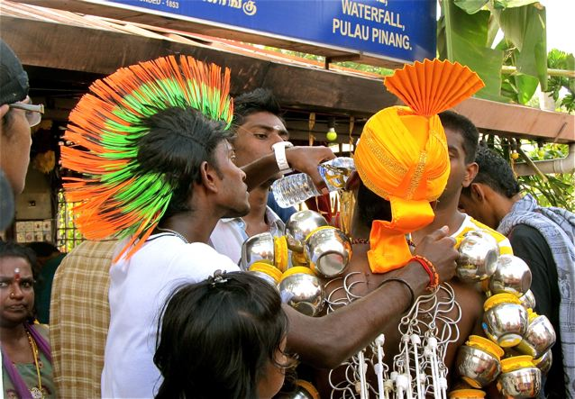 Thaipusam devotee being helped by friends in Penang