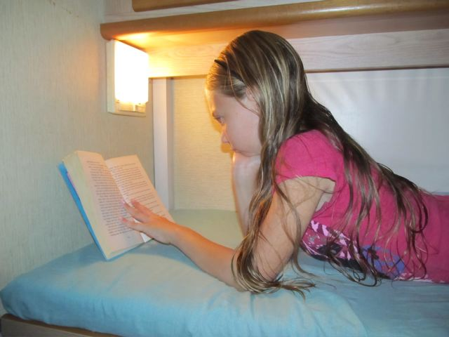 Our girl reading in our campervan as we travel around Europe