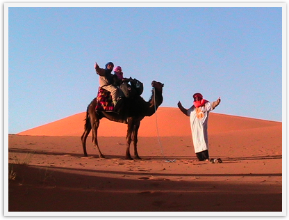 Father and 6 year old daughter doing a camel trek in the Sahara
