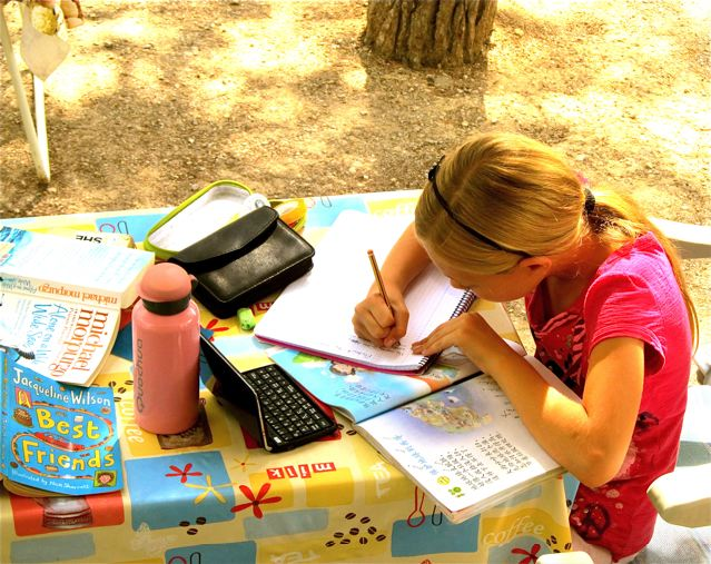 little girl doing Mandarin Chinese homework in Barcelona under the trees