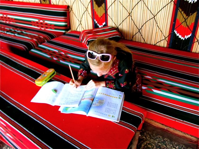 Girl dressed in Bedoin clothes in Wadi Rum doing Chinese homework