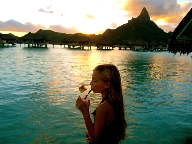 world's Most Well-Traveled Child - sipping tropical drink in Bora Bora sunset