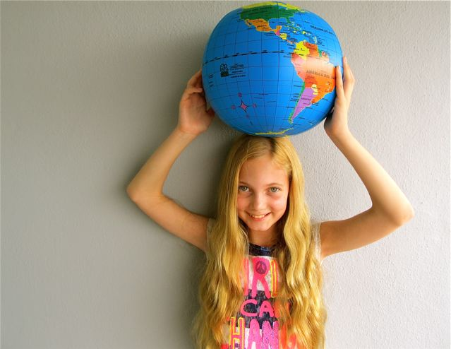 Cute young girl who is world's most traveled kid with the world in her hands