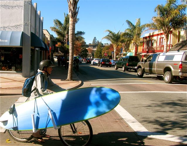 California kid on  a bike with surfboard in beachtown on the ocean