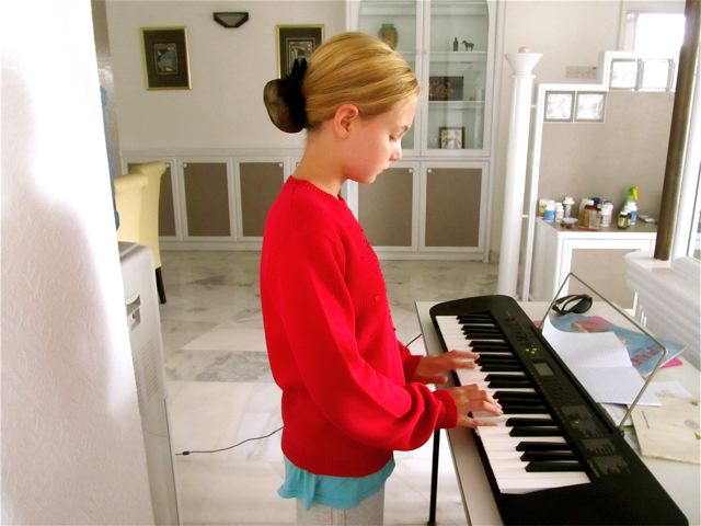 Teen musician Mozart practicing piano in Asia - traveling the world with piano and violin is a challenge