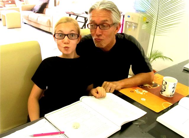 travel tween Mozart doing algerbra and geometry homeschool  in Asia - making geeky faces with fake glasses and  dad
