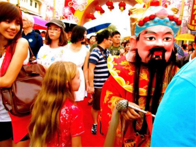Blond American travel kid Mozart in Asia crowd celebrating Chinese New Year