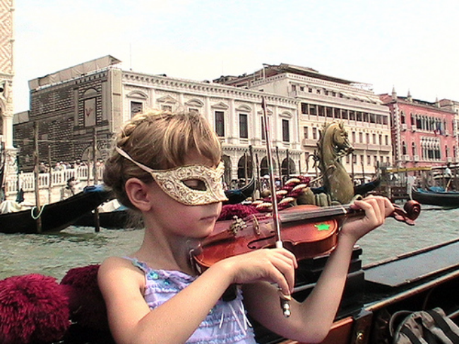 Travel kid Mozart playing violin in  a gondola in Venice