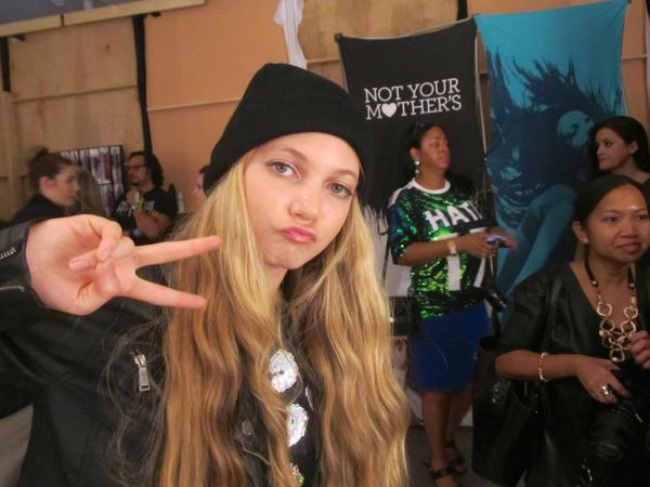 Trlingual teen singer and youtuber Mozart giving the peace sign at New York Fashion Week backstage