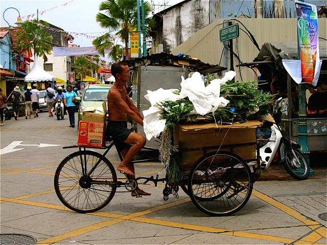 Barefoot Chinese man on loaded rickshaw